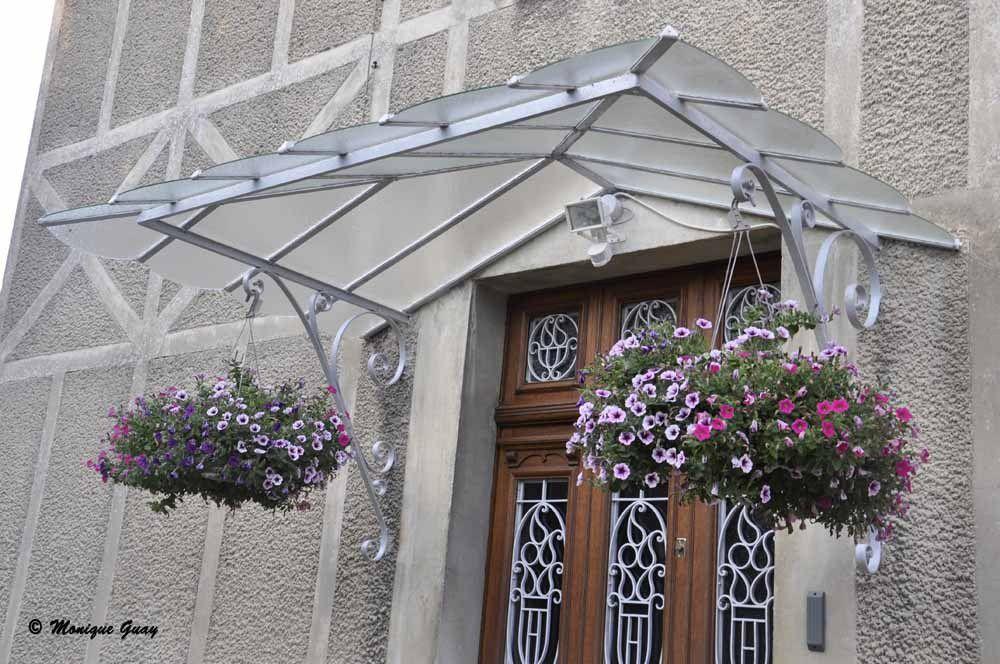 Suspensions de pétunias de chaque côté de la marquise de la porte d'entrée.