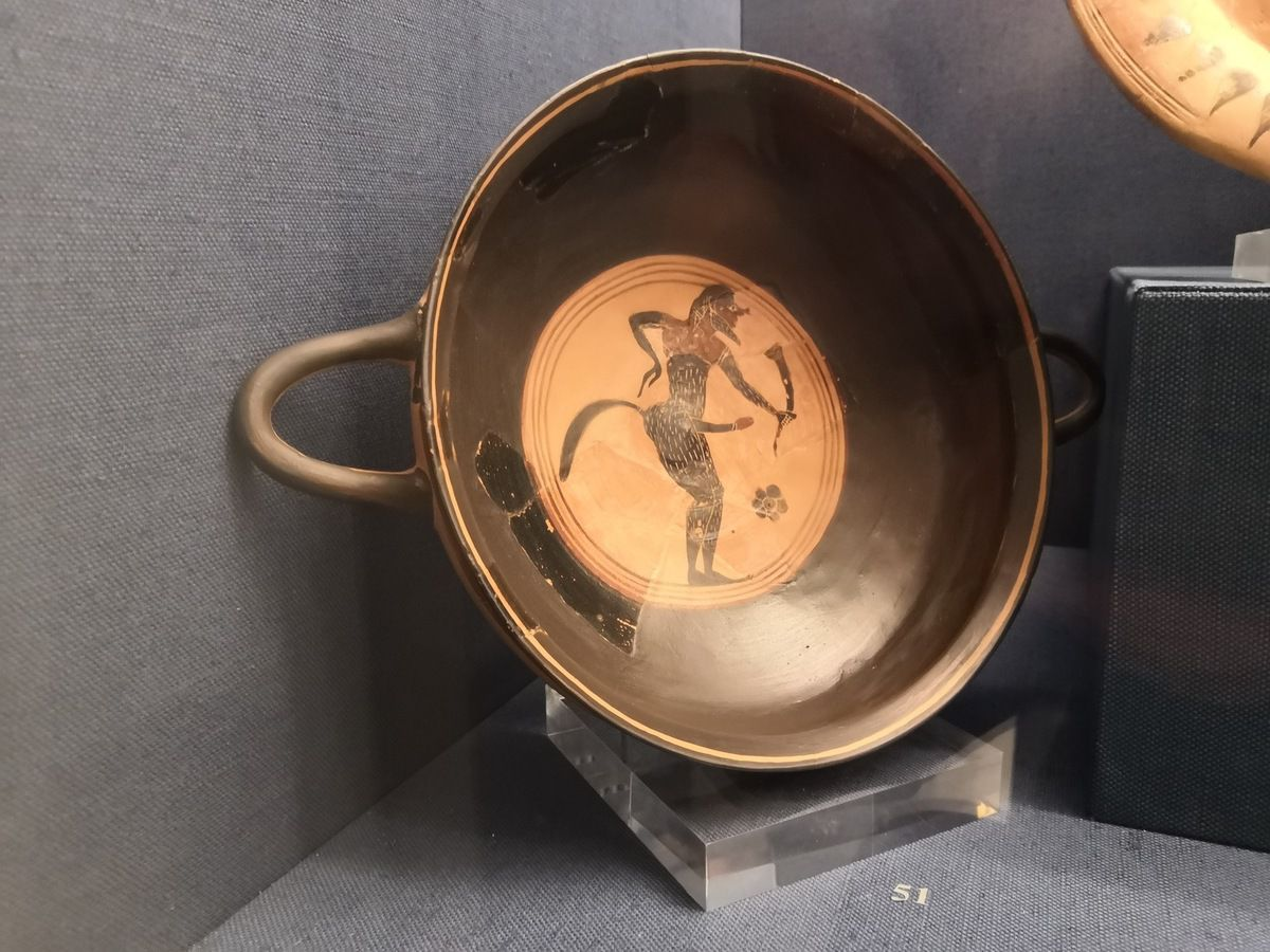 Attic black-figure komast cup. Depicted in the tondo inside is an ithyphallic satyr holding a horn. C. 580 BC.