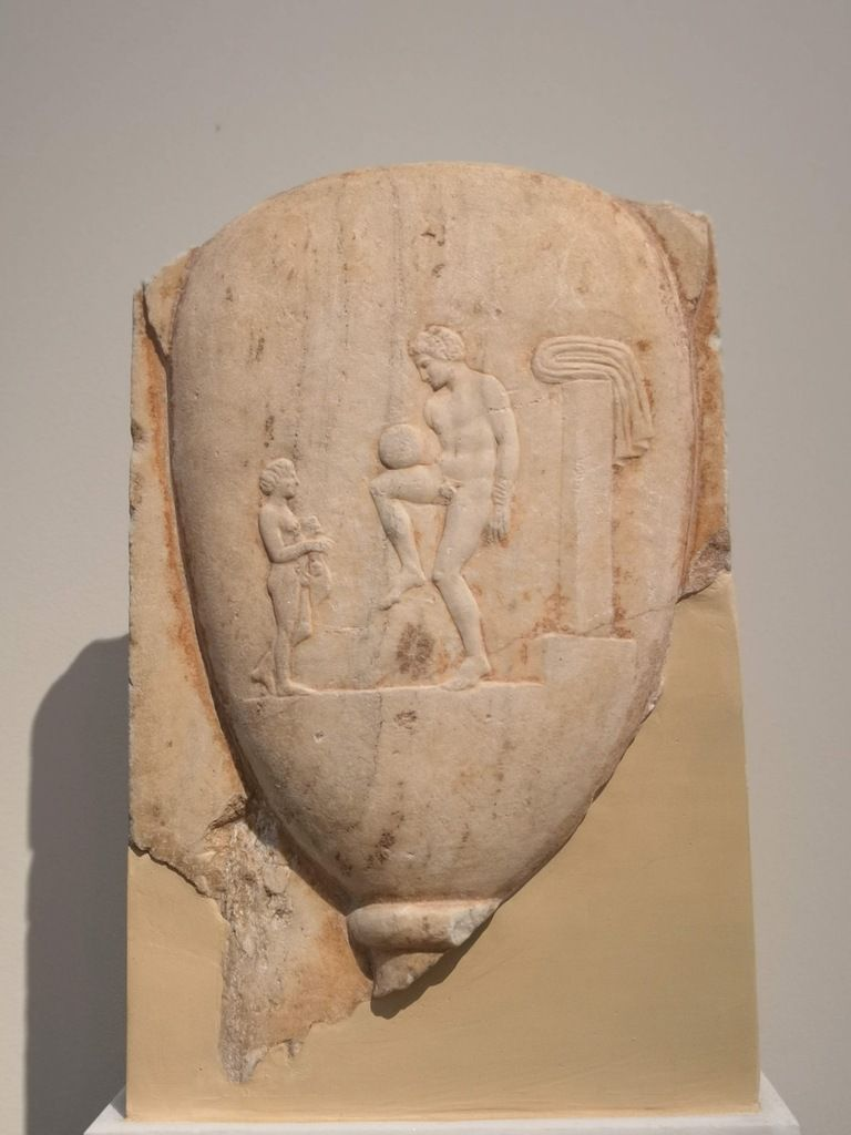 Part of a grave stele. Pentelic marble. Found in Piraeus. [Nude youth in the palaestra watched by his Young servant holding an aryballos and a strigil] 400-375 BC.