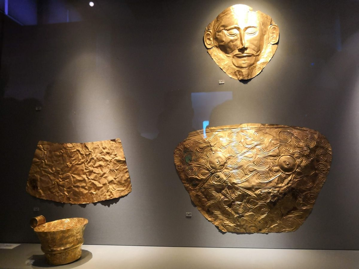 Gold death-mask, known as the 'mask of Agamemnon'. Gold death-mask of a man. Gold funerary breastplates. Gold necklace. Finds from Grave V, Mycenae. 16th century BC.