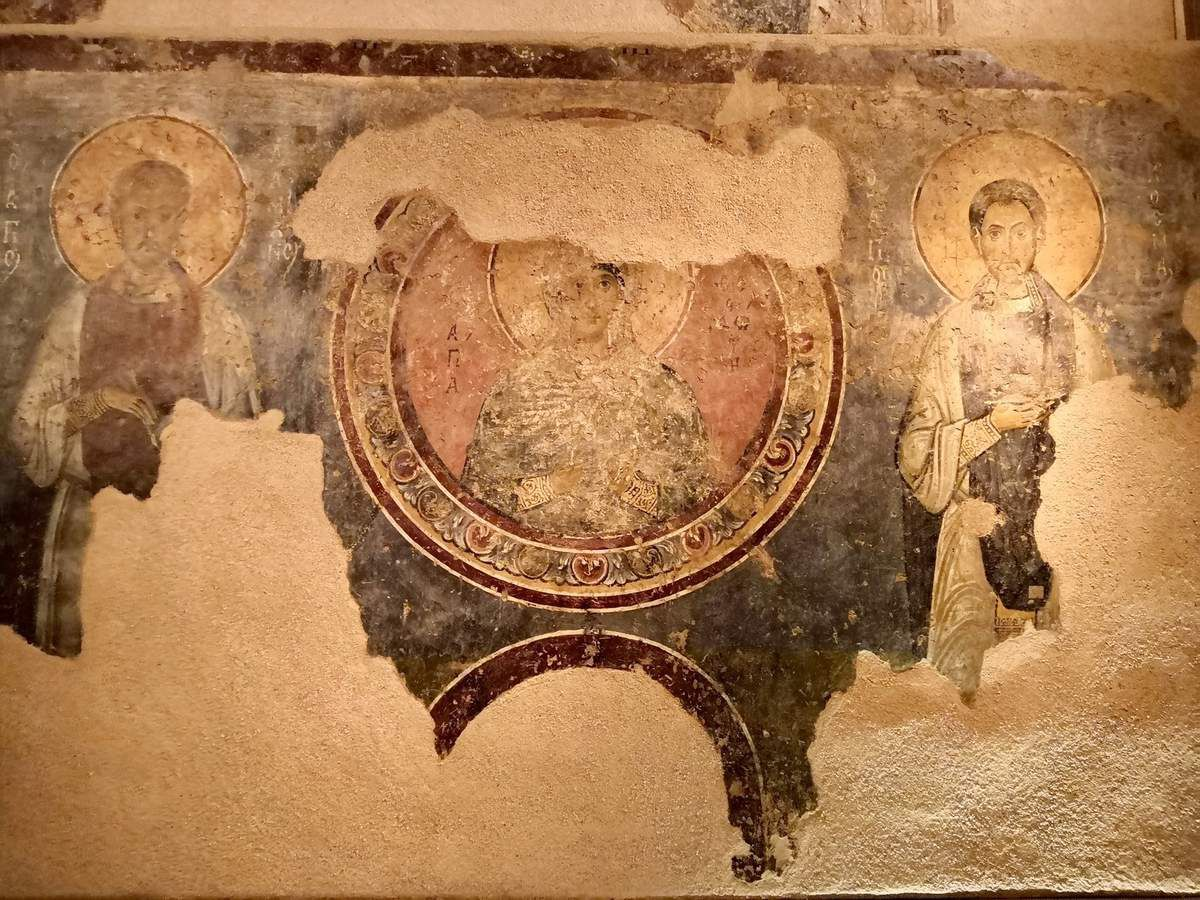 Wall painting with Saints Anargyroi, Theodota and Nicholas, North wall of West cross arm (second layer). 11th c. (Top)