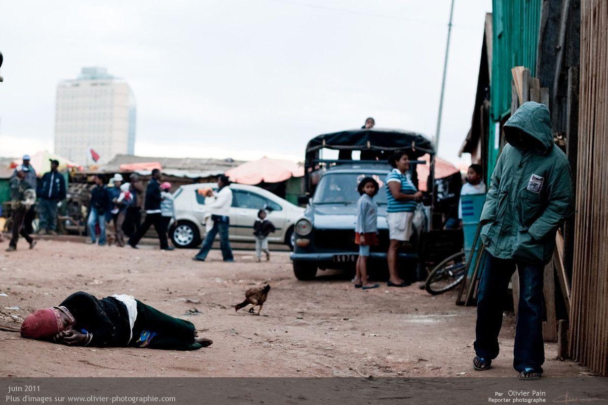 Photo : Une personne encore endormie dans la rue près du marché d'Ivato. L'alcoolisme est un réel problème dans le pays. Beaucoup de personnes déèdent suite à l'ingestion d'alcool frellaté réalisé dans d'anciennes cuves à pétrole ou essence.