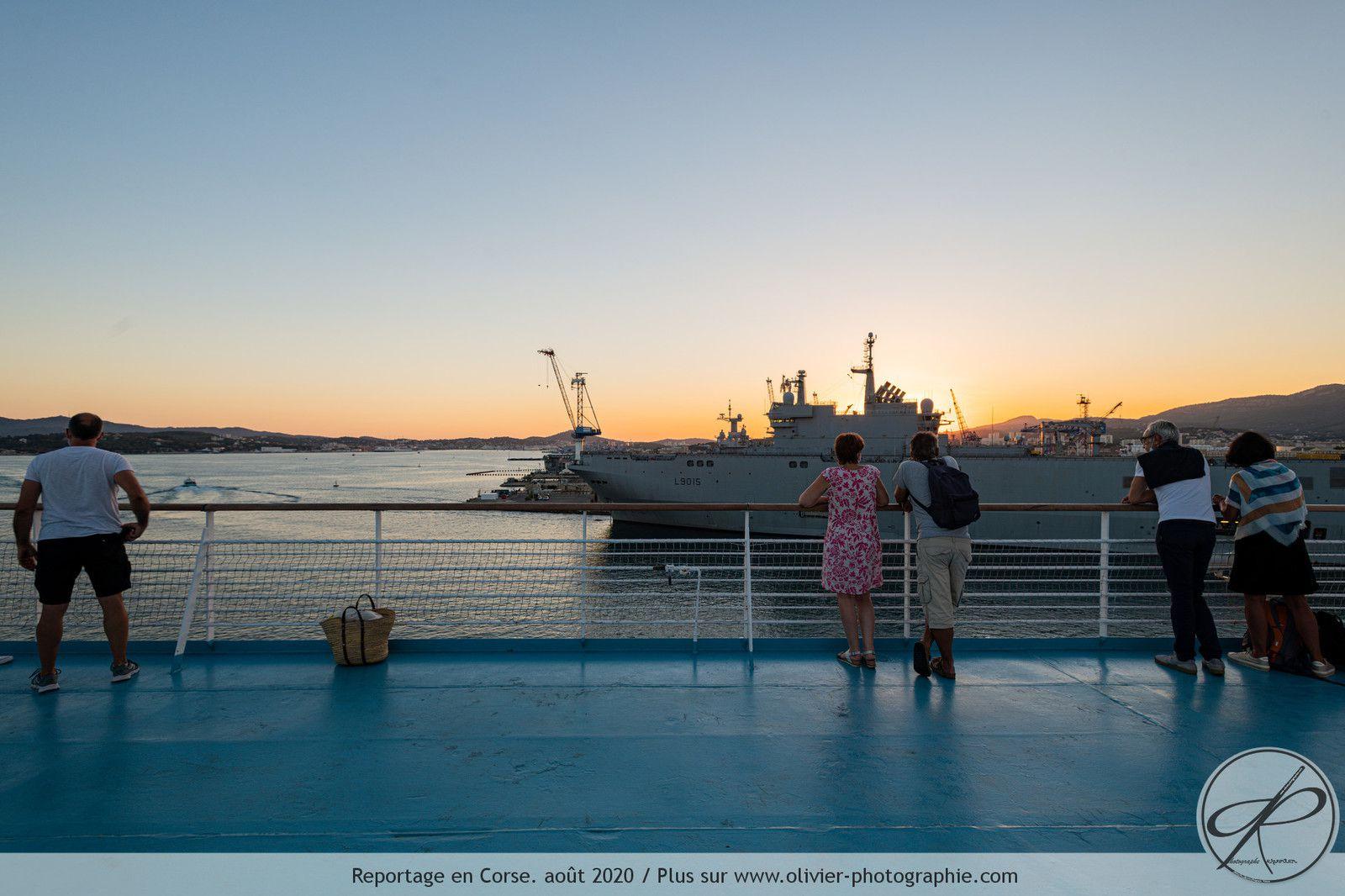 Le départ. Des personnes en train de regarder le port militaire de Toulon depuis le pont le plus haut du ferry.