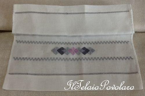 Un asciugamano in lino con motivi a punto reale