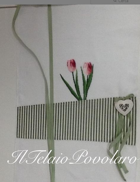 Una tenda in lino bianco con una 'tasca' in cotone a riche  che accoglie due tulipani