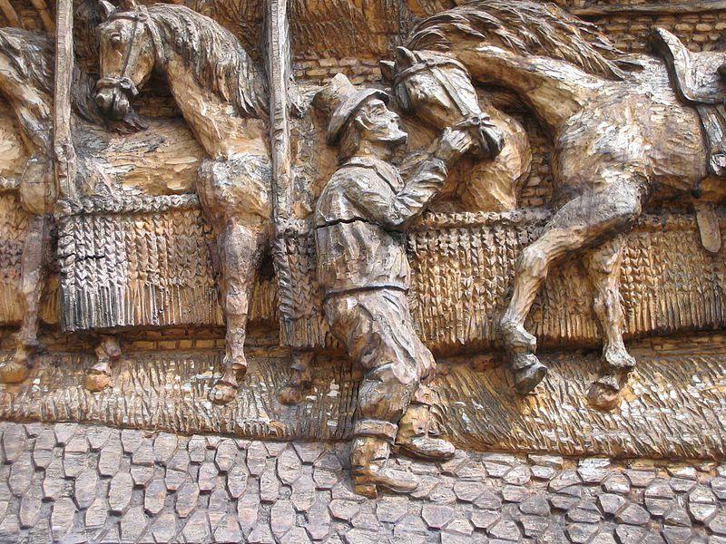 Détail de sculpture sur bois en bas-relief d'un relais de Poste à chevaux de Launois, Ardennes, image Henri Docquin, Wikipédia CC.