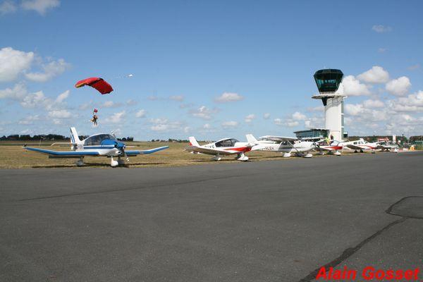 Atterrissage d'un parachutiste derrière la flotte de l'aéroclub.