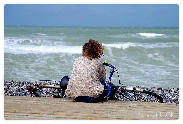 Fille assise sur son vélo au bord des planches de la plage de Cayeux-sur-Mer et regarde la mer
