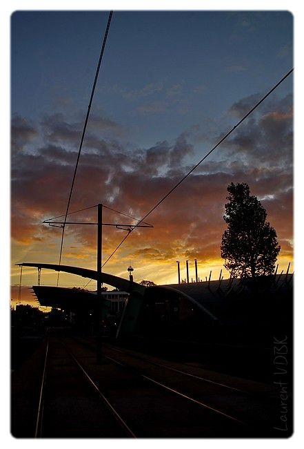 Les rails et la station du métro à Sotteville en contre-jour du ciel rougeoyant...