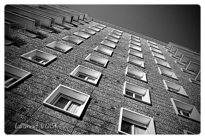 Vue en contre plongée des fenêtres d'un immeuble de l'Espace Marcel Lods à Sotteville-lès-Rouen, sous un angle créatif - Noir et Blanc au fort contraste