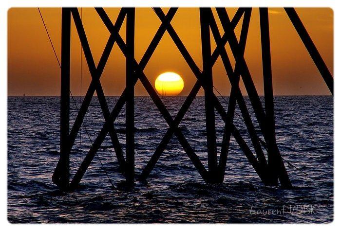 Soleil couchant pris à travers les pieds en croisillons d'une pêcherie. Symétrique et graphique.