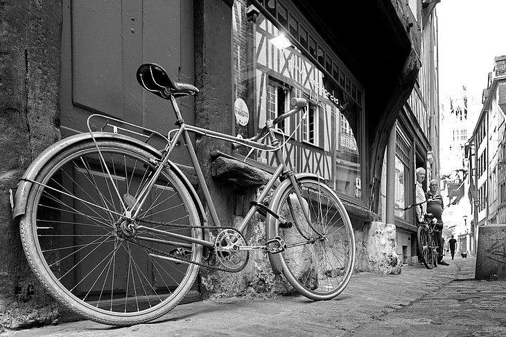Vieux vélo devant la vitrine d'une ancienne boutique authentique rue Damiette (rue pittoresque du quartier historique du vieux Rouen). Photos de rue en noir et blanc, maisons en colombages...
