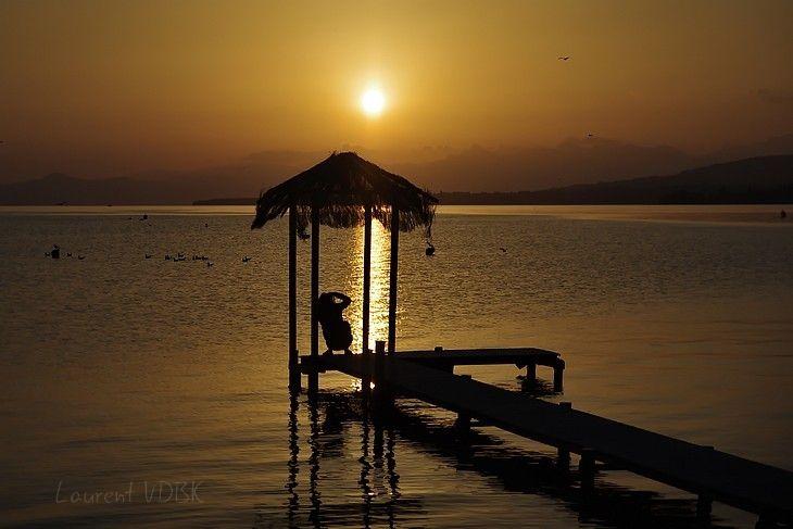 Excevenex : Lever de soleil sur le lac Léman, cabane bambou au premier plan en ombre chinoise et silhouette d'un photographe, montagne au dernier plan
