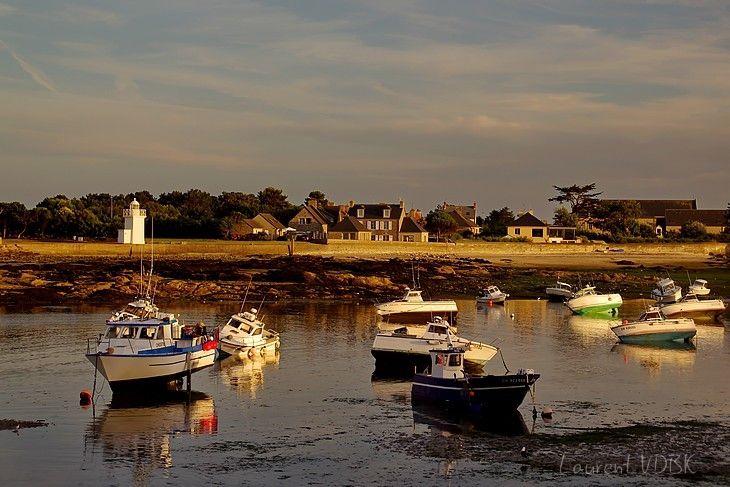 Les petits bateaux échoués dans le port de Barfleur à marée basse, éclairés par la douce lumière dorée du coucher de soleil