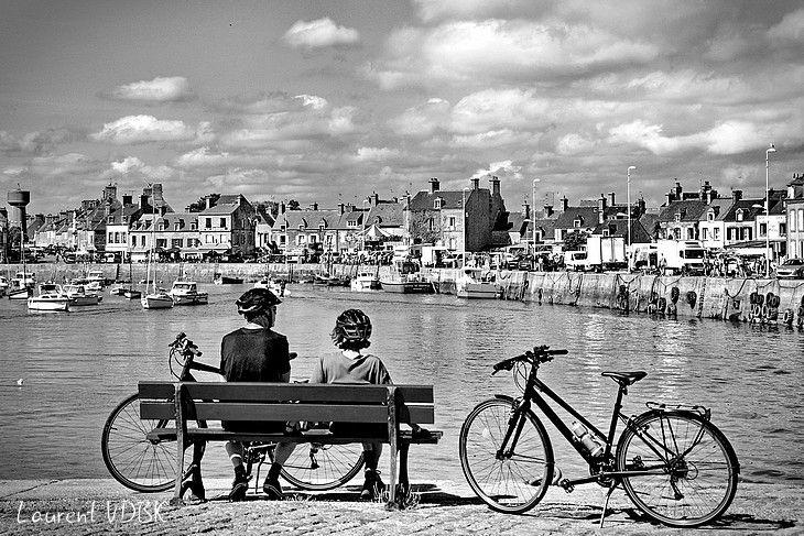 Cyclistes (avec leur casques et leur vélos) assis sur un banc et contemplant le port de Barfleur