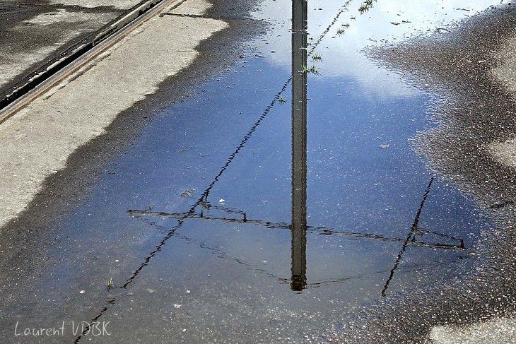 Reflet des caténaires dans une flaque d'eau à Sotteville