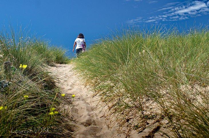 Femme allant à la plage par les dunes de Barneville