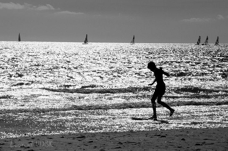 Silhouette d'un enfant qui joue à la mer en contre-jour et noir et blanc