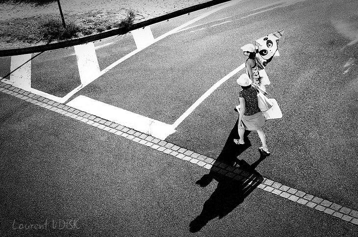 Personnes dans la rue allant vers la mer en contre-jour et noir et blanc