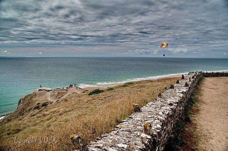 Cap de Carteret avec muret au premier plan et parapente au dessus