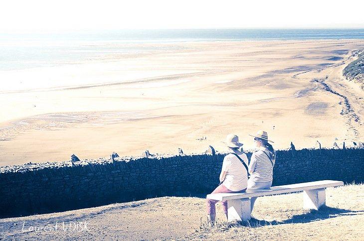 2 personnes assises sur un banc au cap de Carteret et regarde la mer (contre-jour surexposé aux couleurs pastel)