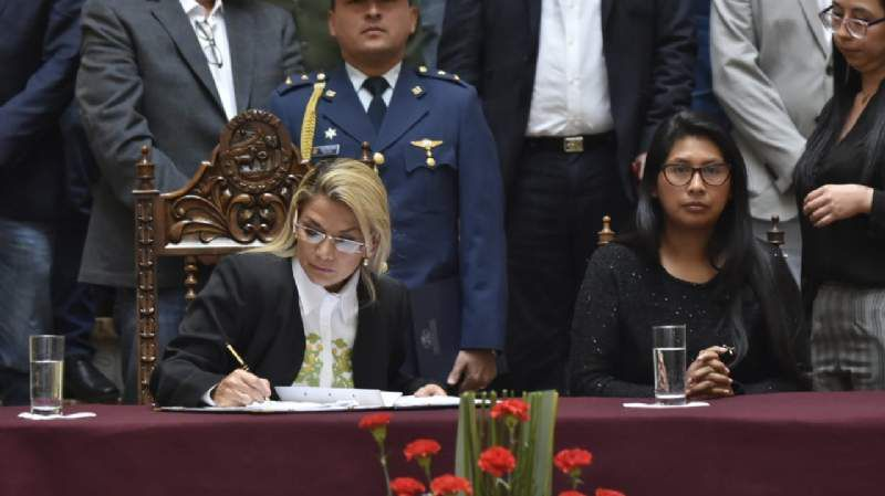 Eva et la présidente de fait signant la loi électorale