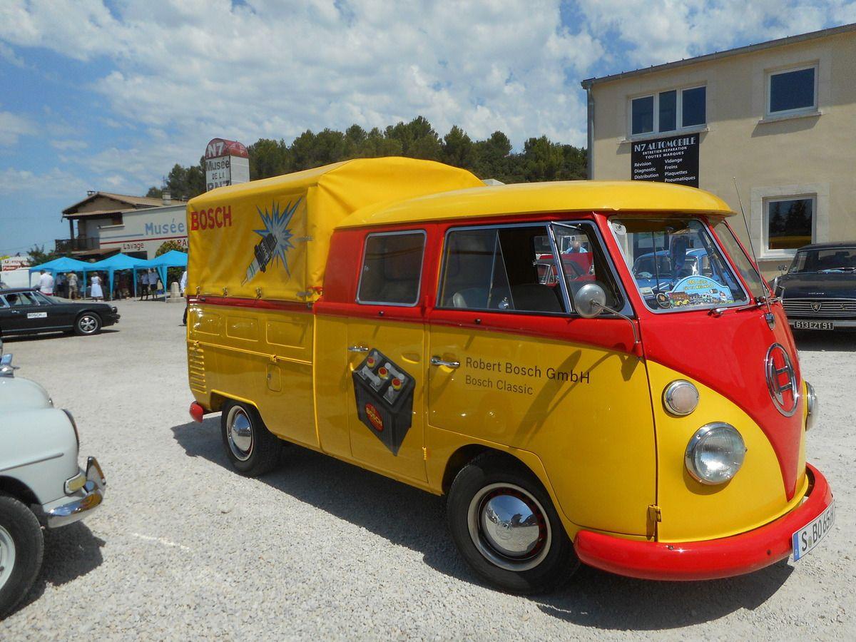 Une camionnette jaune et rouge circule sur le parking du musée de la N7 de Piolenc