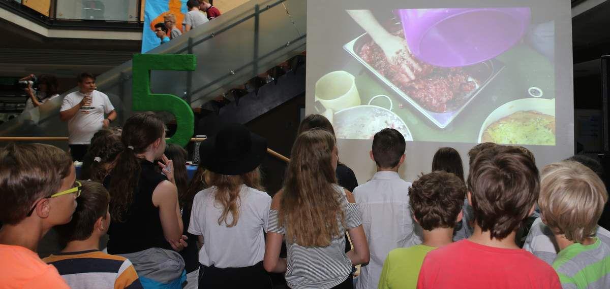 """Moderator Christian Holler aus der Klasse 10 a begrüßte die Schulgemeinschaft auf der Bühne der Aula nach einem Videoclip über fünf Jahre """"Geschichte"""" von Fresh & Fruits-Schülerlounge, stellte die Kreationen und Gewinner von Bagelicious vor und schickte die Teams zum Händewaschen, was die Hygienevorschriften eben verlangen. In dieser Zeit konnten sich alle Teilnehmer der Gesunden Pause auf der Großbildleinwand über die Herkunft und Herstellung der Produkte einen Eindruck verschaffen. Gemüse und Salat stammte von der örtlichen Gärtnerei Klinger, das Hackfleisch und der Italienische Landschinken von der rollenden Landmetzgerei Mohr. Beide sind langjährige Lieferanten der Schülerfirma und traten für dieses Event als Sponsoren auf. Der Pikante Curry-Nuss-Aufstrich und die Fleischbällchen für 150 Bagels wurden im Hause Filbig hergestellt, das Gemüse im Café Punktlandung belegfertig geschnitten. Für Lukas Krenz, Sophie Becker und Helga und Jana Filbig war das Wochenende ausgefüllt von Vorbereitungen für die Gesunde Pause."""