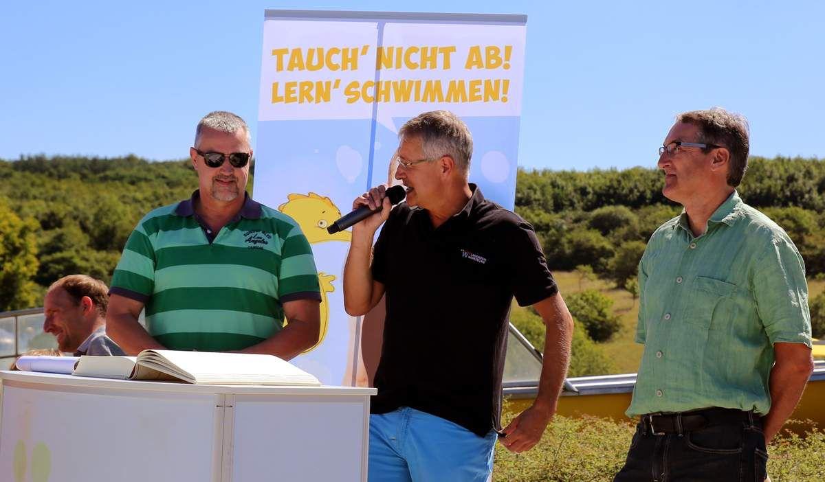 """Schulrat Ingo Matschullis aus Veitshöchheim (links), lobte das Projekt """"Tauch nicht ab! Lern Schwimmen"""" des Landkreise und freute sich über das den Schulsport fördernde Event. In der Bildmitte stellte der scheidende Leiter der Servicestelle Sport des Landkreises, Hermann Gabel (Bildmitte),der souverän das Schwimmevent moderierte, seinen Nachfolger Klaus Rostek vor, der ebenfalls ein Veitshöchheimer ist."""