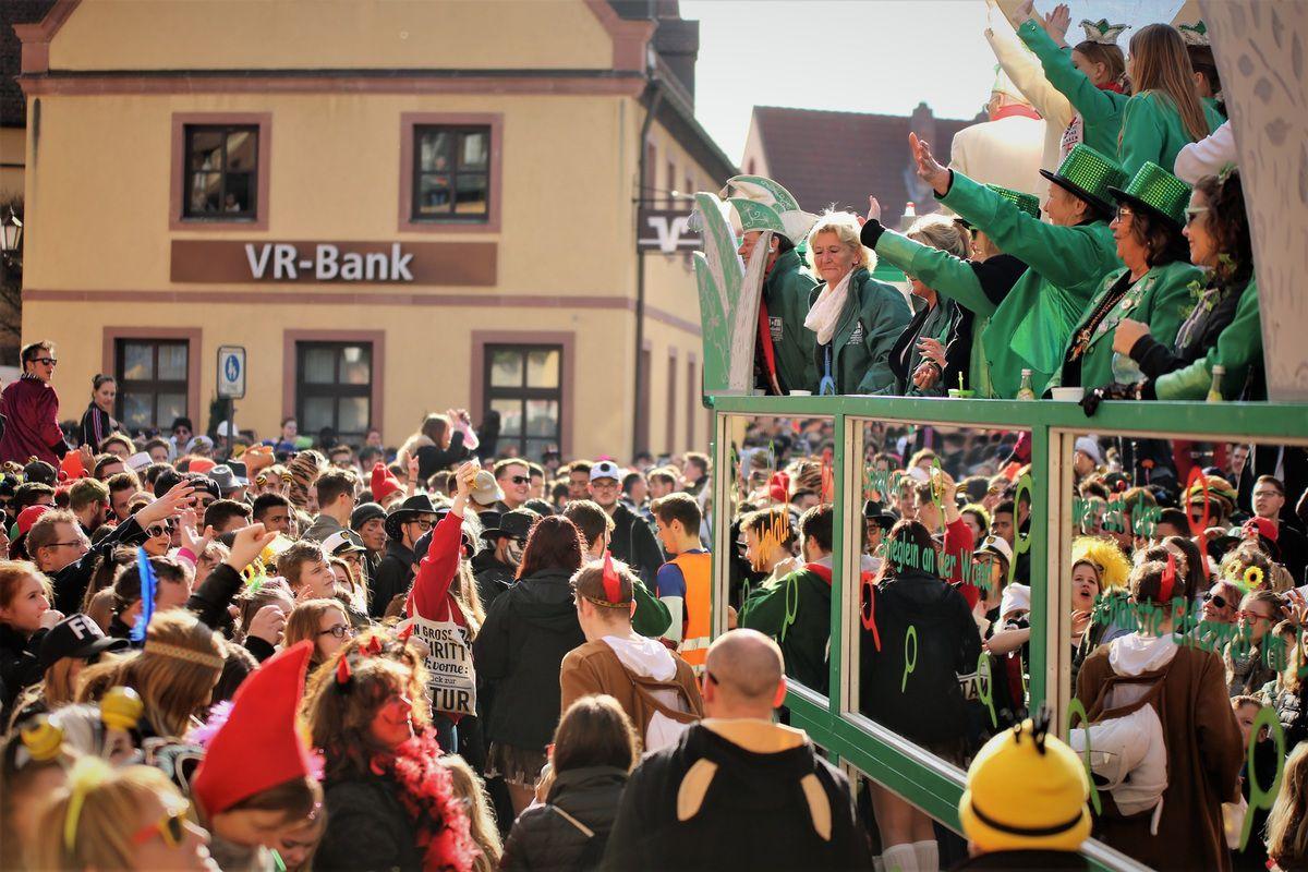 """Im Zentrum an der Vituskirche in der Kirchstaße, wo eine große Menschenmasse dicht zusammengedrängt dem farbenprächtigen Gaudiwurm zujubelte, herrschte eine Riesenstimmung. Für all die kleinen Narren flogen zentnerweise Bonbons und andere Leckereien in die Menge.  Hier schallte immer wieder """"Veitsöche Helau"""" aus Tausenden von Kehlen, animiert durch Rudi Hepf, der die Zugfolge moderierte und alle Aktiven hochleben ließ."""