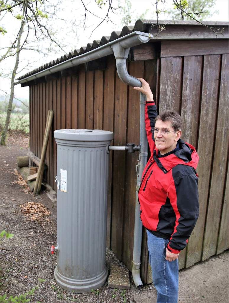 Hier zeigt Vorsitzender Burkard Löffler auf die an der Schutzhütte aufgestellte 330 Liter-Regentonne, die nach erfolgter Reinigung der Dachflächen sauberes Regen-Wasser zum Händewaschen liefert.