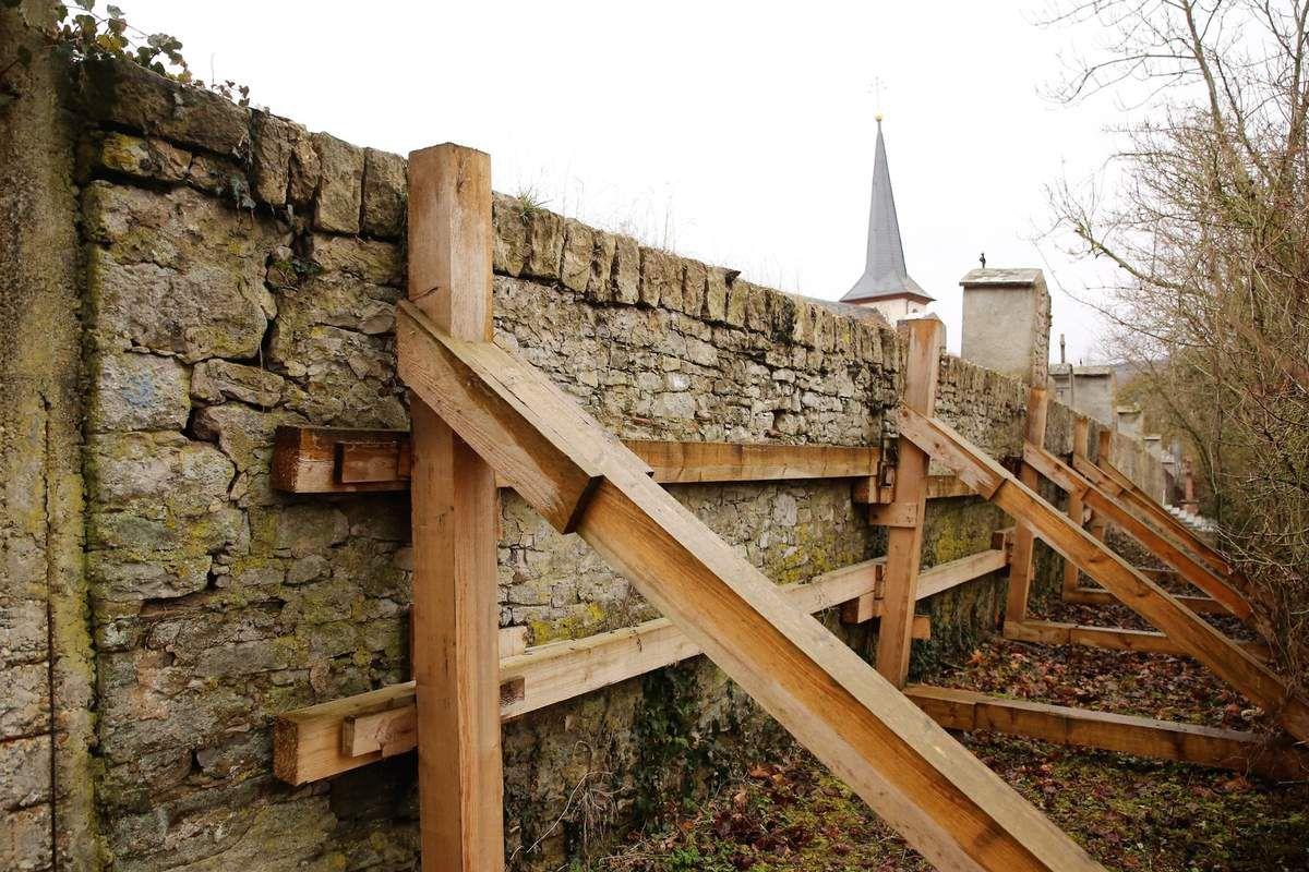 Der Bauhof der Gemeinde hatte deshalb als kurzfristige Sicherungsmaßnahme diese Mauer durch eine Holzkonstruktion provisorisch abgestützt.