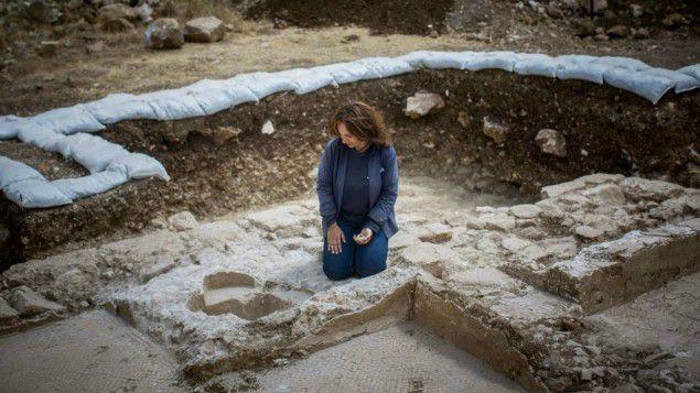 Annette Nagar des Autorité d'Antiquités israéliennes regarde le font baptismal de l'église d'époque byzantine découverte à Abu Ghosh pendant l'extension de l'autoroute Jérusalem-Tel-Aviv, juin 2015.