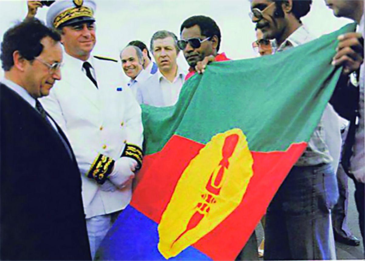 Après sa création et adoption au Congrès de l'UC (Union calédonienne) tenu en 1983  à Ouvéa, présentation du drapeau du «Pays Kanak» par Yeiwene Yeiwene et Éloi Machoro au secrétaire d'État à l'Outre-mer Georges Lemoine lors d'une visite ministérielle en1984 en Nouvelle-Calédonie.  La flèche faitière est de couleur rouge avant de passer au noir. Le drapeau du «Pays Kanak» deviendra le drapeau de «Kanaky» le 1er décembre1984. Après la signature des accords de Matignon en 1988, il est appelé communément drapeau du «FLNKS» (Front de libération nationale kanak socialiste). © éditions de la Province des îles Loyautés