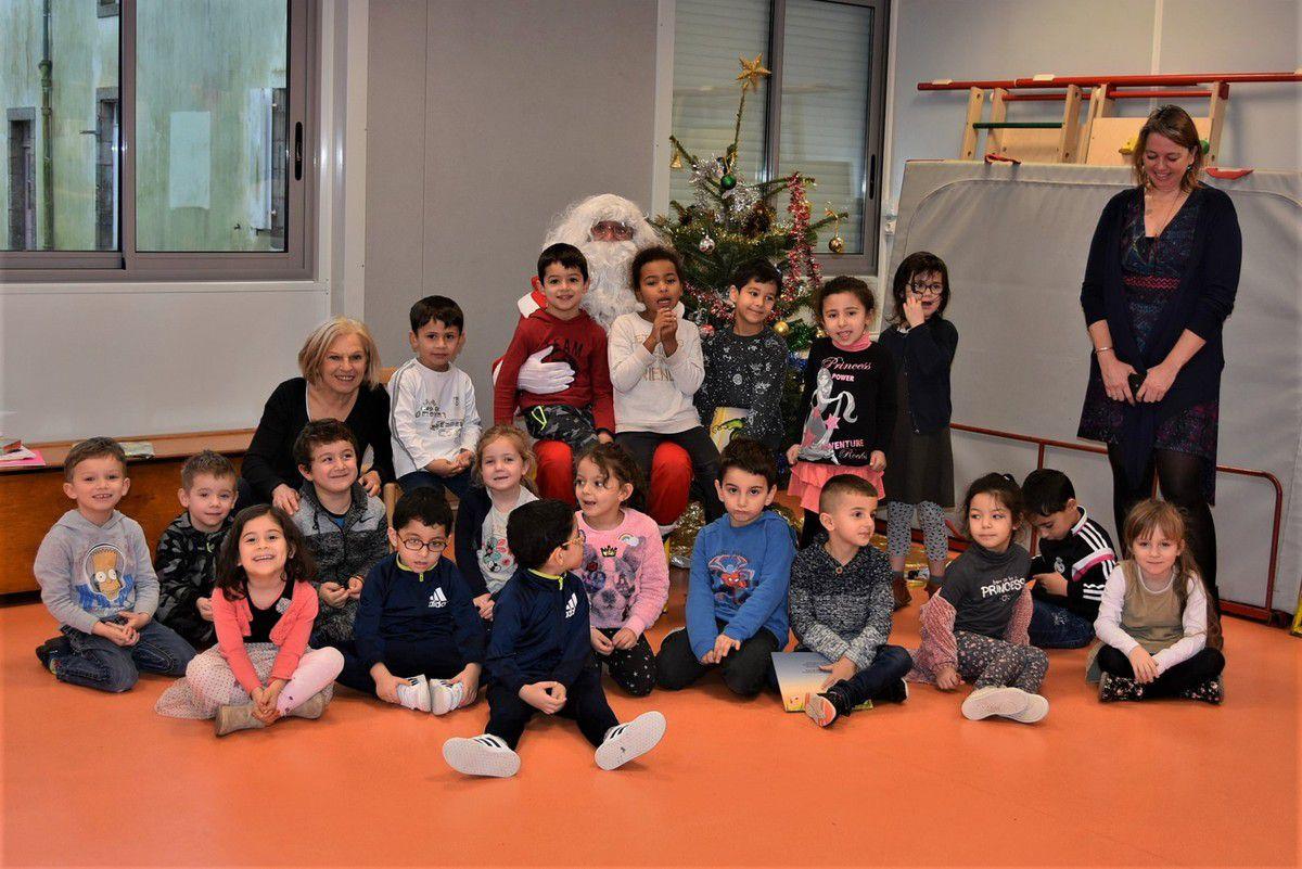 Des enfants roses de bonheur autour du père Noël de l'école du bourg de Penhars