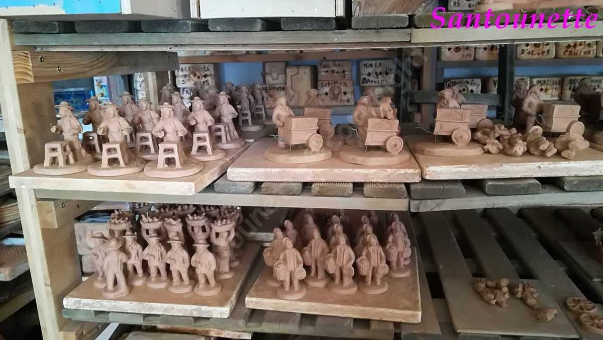 Sur des échelles en bois des réalisations en attente de cuisson.