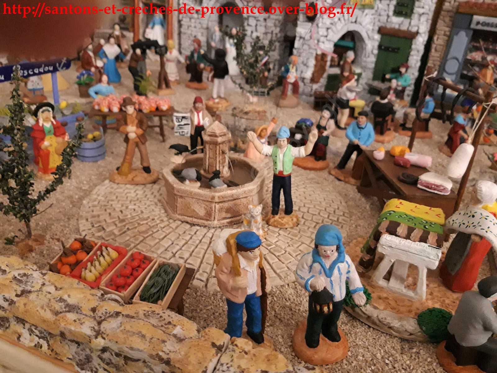 Un marché animé avec la place pavée et le Ravi qui étonné de voir tout ce monde lèvre les bras au ciel.