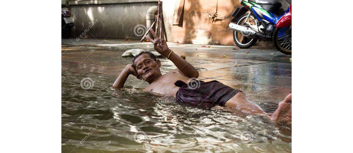 Homme dormant dans la rue (inondations de Bangkok du 29 octobre 2011)