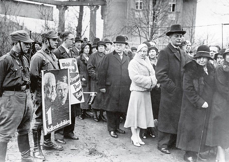 Un mois après son arrivée au pouvoir, Hitler organise des élections législatives. Sur cette photo, on voit le ministre de l'économie Alfred Hugenberg (avec un chapeau melon) devant un bureau de vote berlinois où des nazis intimident les électeurs. © akg-images
