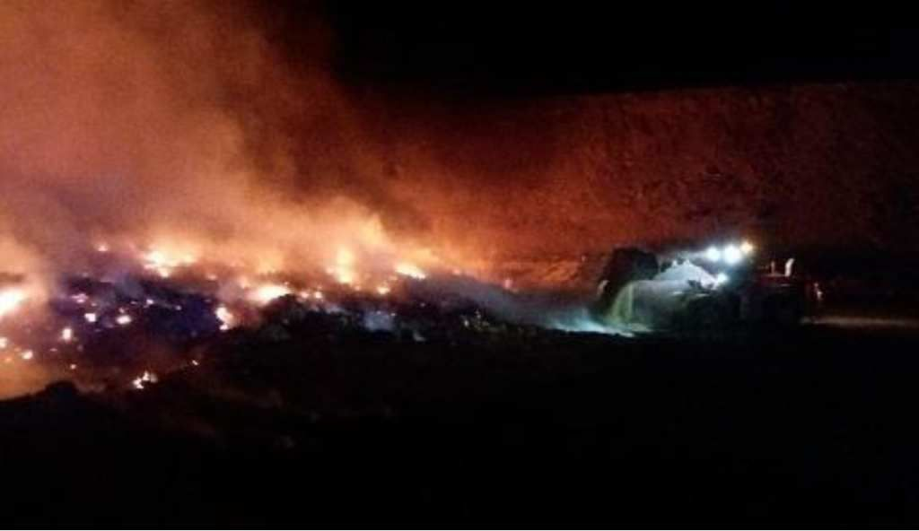 Les engins de la REP rabattent de la terre par-dessus les matériaux en feu.