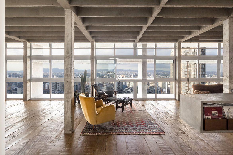 Un appartement avec parquet au sol et béton brut