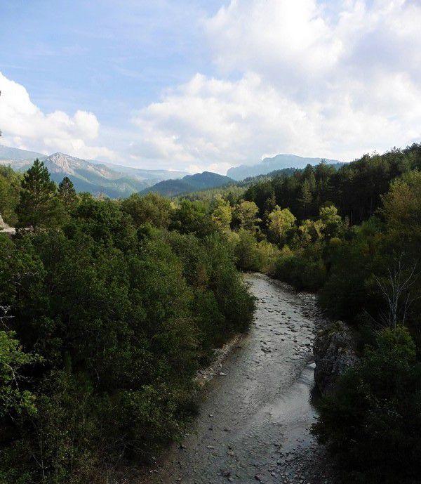 et ça , la vallée du Vançon , en amont , vue depuis le pont . Saint-Symphorien est à droite , Saint-Geniez à gauche , et loin , loin , derrière les montagnes , c'est Verdaches .