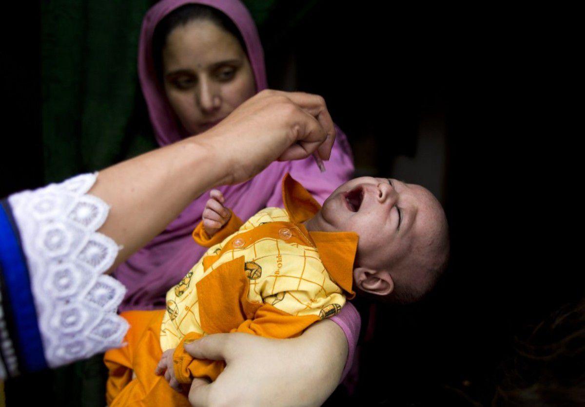 Un agent sanitaire administre un vaccin polio oral à un petit Pakistanais