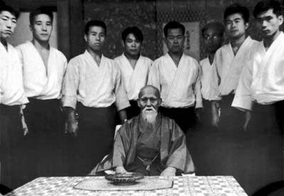 Osenseï entouré d'uchi-deshis. De gauche à droite Kurita Yutaka, Shimizu Kenji, Saotome Mitsugi, Kanai Mitsunari, Toheï Akira, Ueshiba Kisshomaru, Maruyama Shuji, Watanabe Nobuyuki