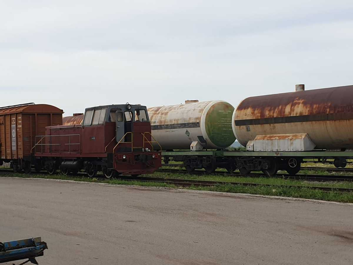 Au Kazakhstan, le 11 juillet 2019, sur l'embranchement particulier d'une entreprise de production d'éthanol près de la ville de Taïynsha, un locotracteur tout neuf côtoie des wagons citernes très rouillés (inquiétant !).