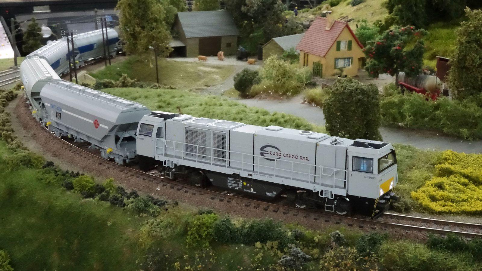 Passage dans la rampe en courbe de la ferme d'un train complet de wagons céréaliers tiré par une loc G 2000 d'ECR.