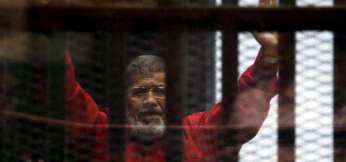 Morsi con uniforme rojo alzando los brazos como las alas del Fénix