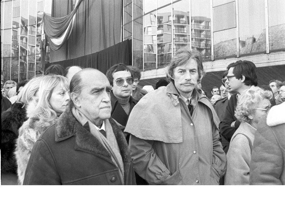 JEAN FERRAT ET OSCAR NIEMEYER (au premier plan) SUR LE PARVIS DU SIÈGE DU PARTI COMMUNISTE FRANÇAIS (PCF) LORS DE LA CÉRÉMONIE EN HOMMAGE A LOUIS ARAGON LE 28 DÉCEMBRE 1982.