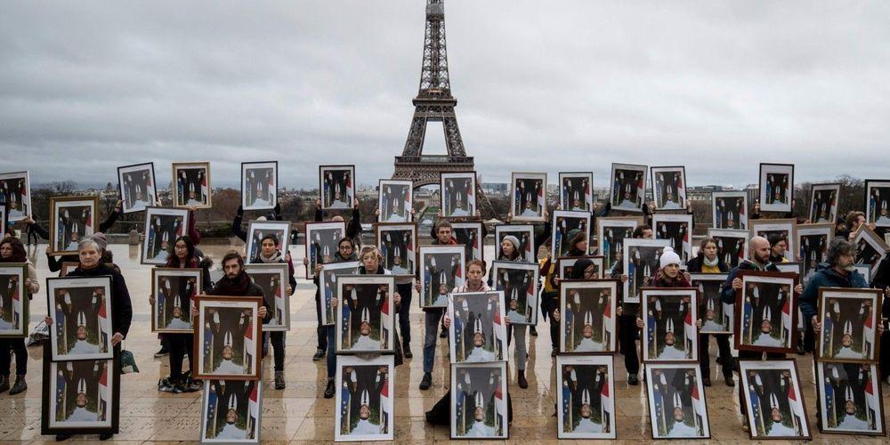 Cent portraits du Président de la République dérobés dans les mairies de l'Hexagone ont été brandis dimanche 8 décembre à Paris pour dénoncer l'inaction du gouvernement en matière de lutte pour l'environnement. THOMAS SAMSON/AFP