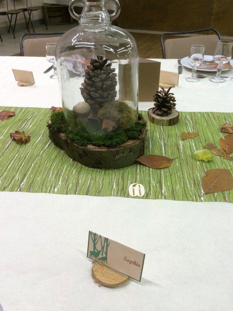 Sous les cloches en verre, une composition faite de mousse, de pommes de pin, de champignon en bois et d'un petit animal, le tout posé sur un rondin de bois.